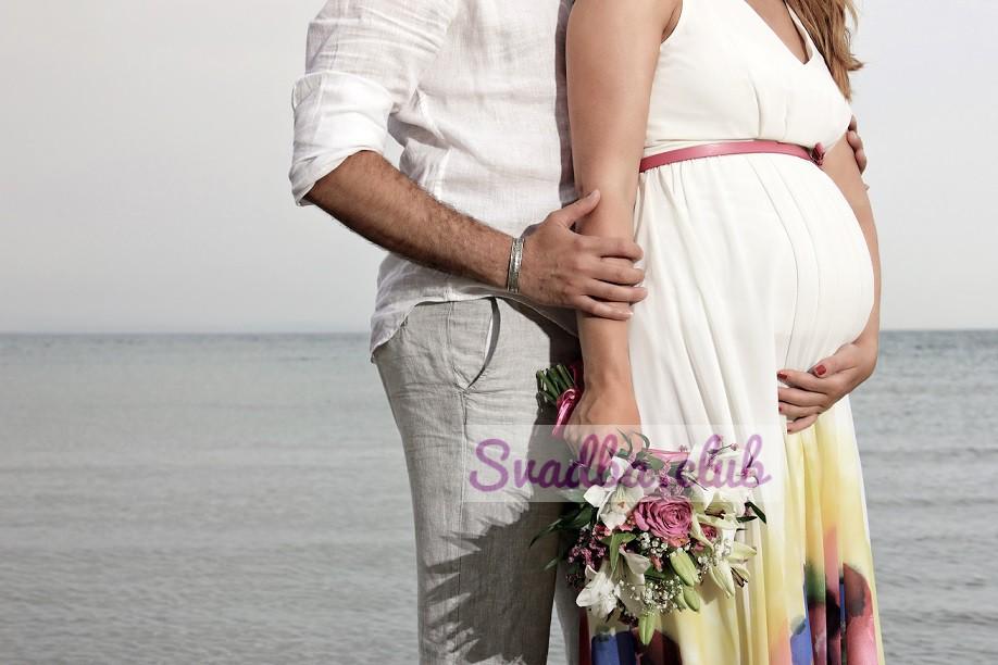 жених и беременная невеста обнимаются