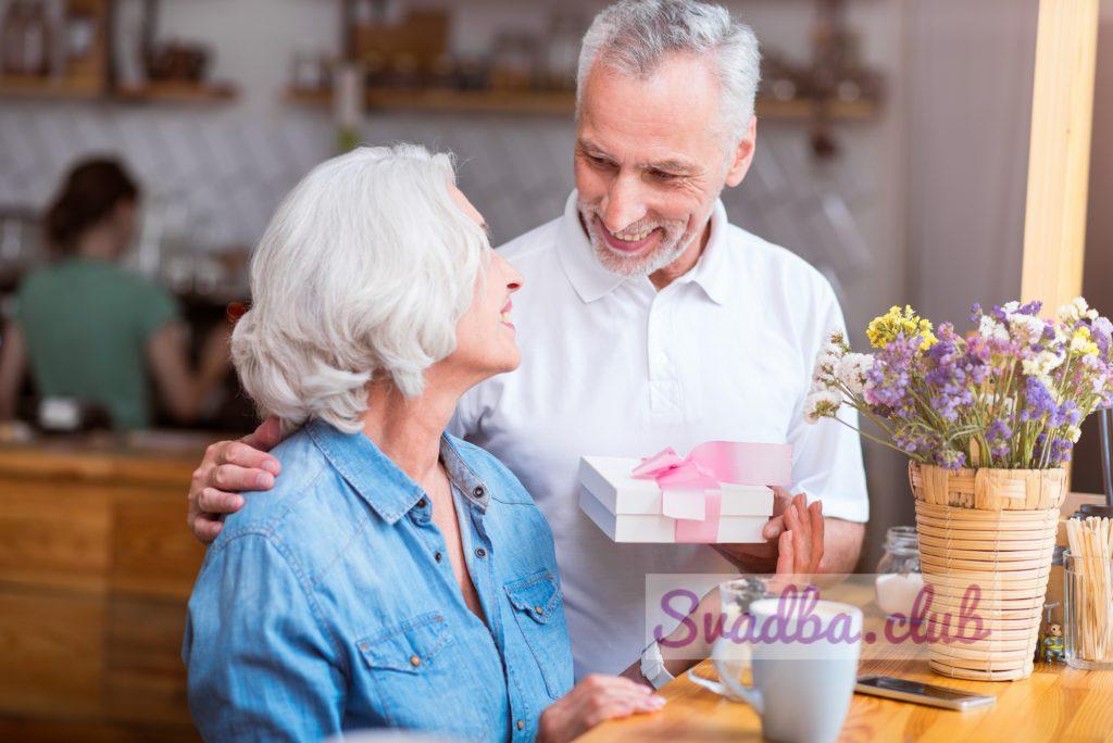 Для тебя моя любовь. Привлекательная женщина улыбается, сидя за столом, пока ее муж дает ей подарок, отдыхая в кафе вместе